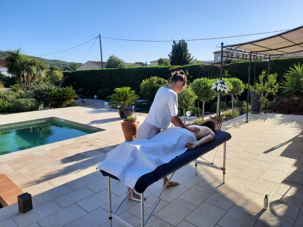 Sports recovery Massage on the sun terrage by the pool for professional swiss freestyle skier.