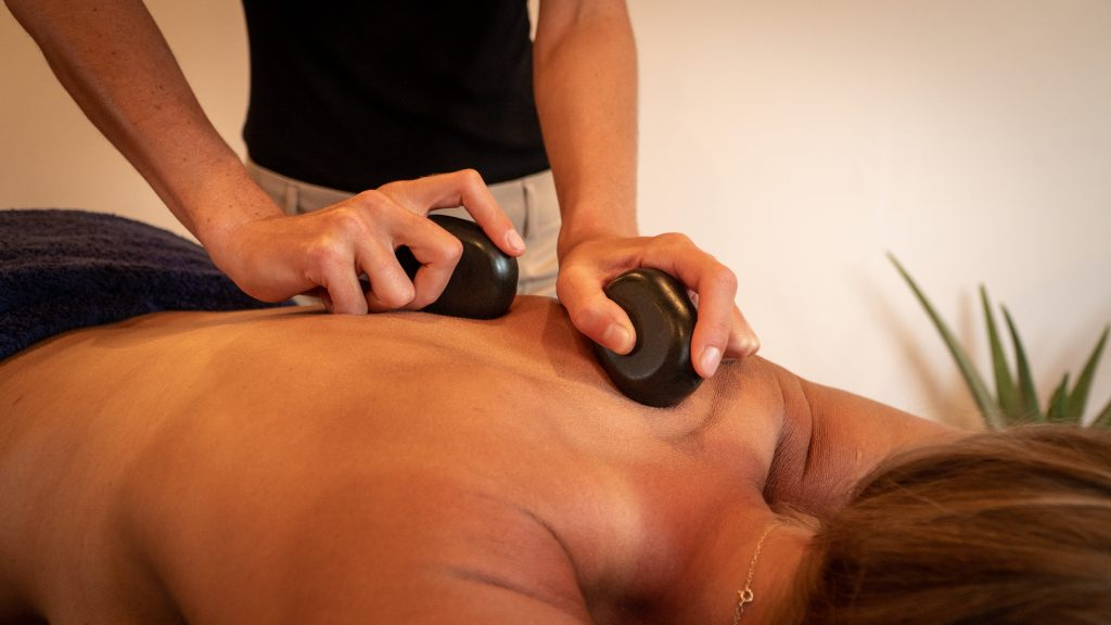 Moving hot stones on your back. Relaxing hot stone massage