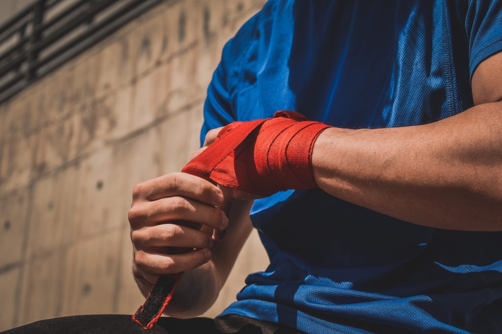 sports wrist injury. Man in blue top with a sports strap who has been injured