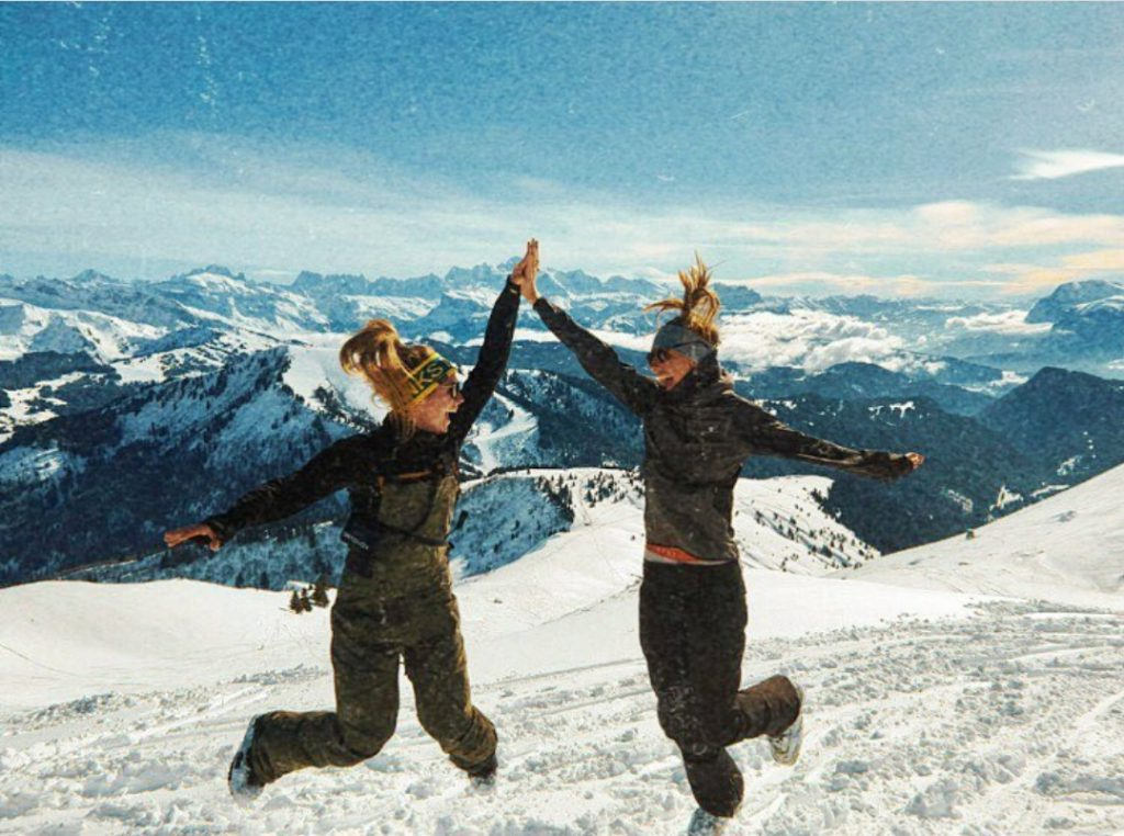 skiers high five on the mountains.