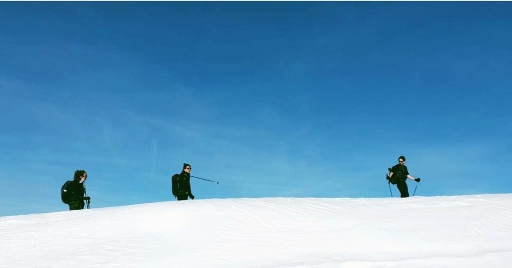 3 people ski touring and splitboarding on the mountain. blue sky