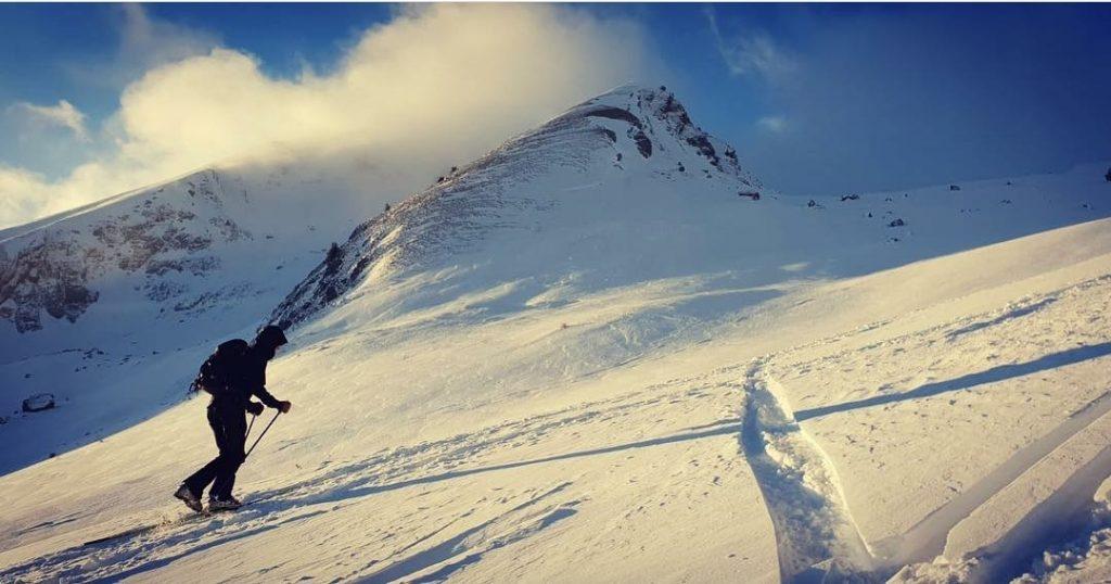 ski touring up a mountain face at sunset